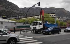 Un camió amb la grua aixecada trenca un panell informatiu