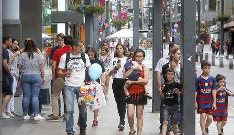 Alguns turistes passegen i fan compres en l'avinguda Meritxell.